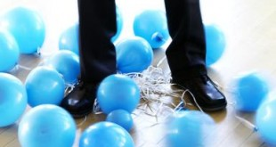 businessman's legs entangled with deflated balloons