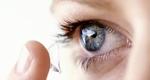 YOUNG WOMAN PUTTING CONTACT LENS IN EYE